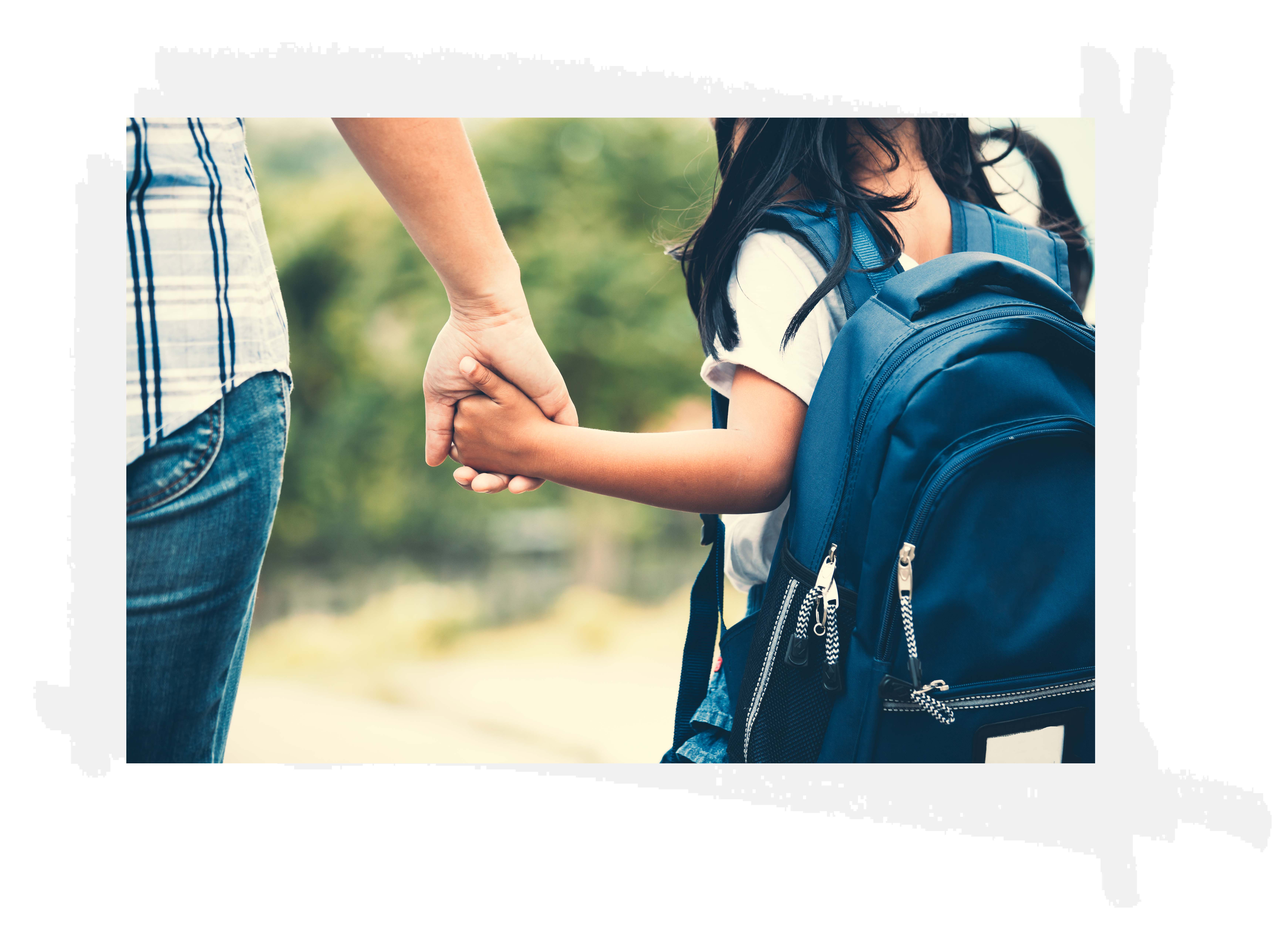 parent holding child hand on way to school
