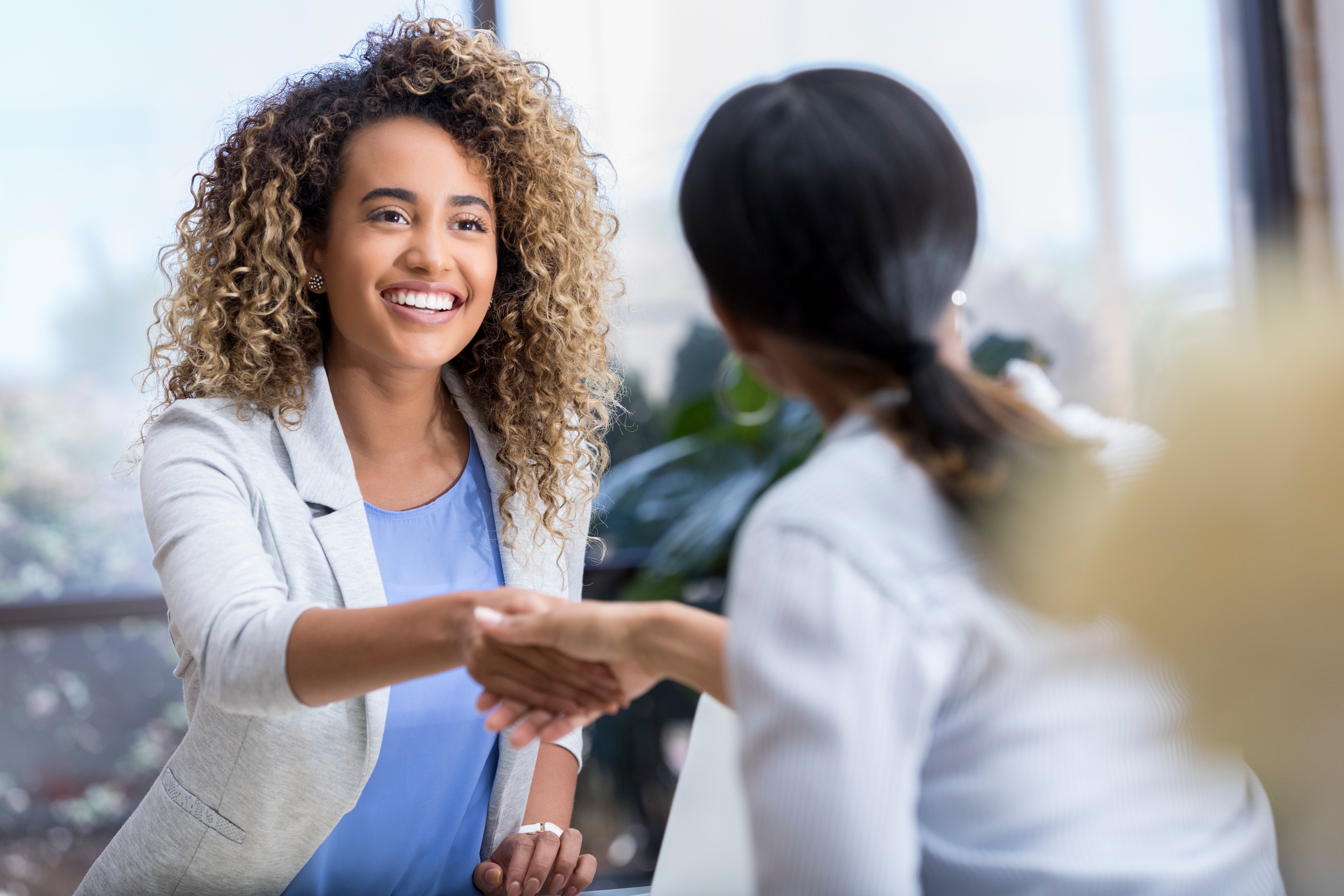 Young businesswoman greets colleague
