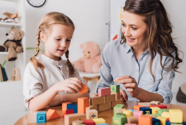 happy mother playing blocks with adorable little child